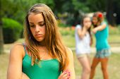 Two Teenage Girls Making Fun Of The Third
