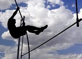 image of track field  - An athlete attempts a pole vault while silhouetted by the sun against a cloudy sky - JPG