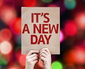 It's a New Day written on colorful background with defocused lights