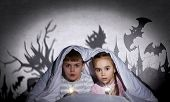Two little kids with flashlight under blanket