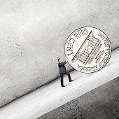 Businessman rolling big one cent coin