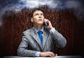 Young troubled businessman sitting under rain and talking on phone