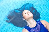 Young hispanic woman with long black  hair, floating back in the blue swimming pool