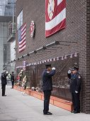 NEW YORK - SEPT 11, 2014: Firefighters salute during the changing of the guard at the Memorial Wall at FDNY Engine 10 Ladder 10 House on Liberty St . The firehouse is directly across from the WTC.