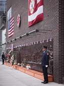 NEW YORK - SEPT 11, 2014: A firefighter stands guard at the Memorial Wall at FDNY Engine 10 Ladder 10 House on Liberty St . The firehouse is directly across from the WTC site.