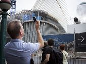 NEW YORK - SEPT 11, 2014: A man takes a picture of the Freedom Tower and structures at the WTC site on the anniversary of the 2001 September 11 terrorist attacks in Lower Manhattan.