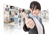 Confident Asian business woman give you a excellent sign standing in front of TV screen wall, closeup portrait.