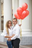 Loving couple on a city street with balloons.