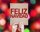 Merry Christmas (In Spanish) card written on colorful background with defocused lights