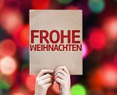 Merry Christmas (In German) card written on colorful background with defocused lights