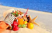 Woman Hat, Different Fruits, Starfish And  Glass Of Juice On The Sand On The Beach