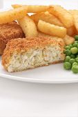 stock photo of potato chips  - Fishcake made with crumbed fish and potato served with chips and peas - JPG