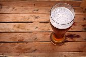 picture of wooden crate  - Tall glass of amber beer standing in an old dirty wooden crate  - JPG