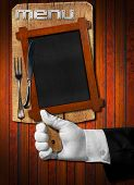 picture of hand cut  - Hand of waiter with white glove holding a old wooden cutting board with empty blackboard and silver cutlery on wooden dark background - JPG