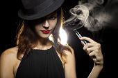 stock photo of tobacco smoke  - woman smoking or vaping an electronic cigarette to quit tobacco - JPG