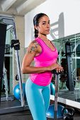 brunette girl with barbell posing at gym after workout