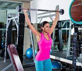 brunette girl wide grip barbell shoulder press workout at gym