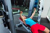 Bench press woman on flat multipower Smith machine workout exercise at gym