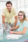 Portrait of a woman wearing headphone and her colleague in office