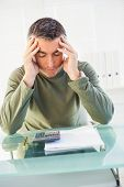 Concentrated man with hands on his head in his office