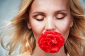 Sensual Tender Young Woman Portrait With Breeze Hair And Rose In Mouth