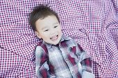 Cute Young Mixed Race Boy Laughing On Picnic Blanket Outside.
