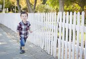 Cute Young Mixed Race Boy Walking with Stick Along White Fence.