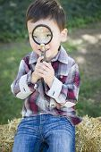 Cute Young Mixed Race Boy Looking Through Magnifying Glass Outside on Hay Bale.