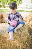 Cute Young Mixed Race Boy Sitting on Hay Bale Putting Coins Into Pink Piggy Bank.