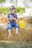 Cute Young Mixed Race Boy Laughing with Sunglasses and Hard Hat Outside Sitting on Hay Bale.