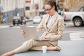 Young businesswoman using her laptop outside in the city