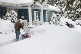 pic of heavy  - Man using snowblower to clear deep snow on driveway near residential house after heavy snowfall - JPG