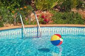 pic of pool ball  - Beach ball floating in summer swimming pool with vintage feel - JPG