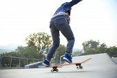 picture of skateboarding  - skateboarder jumping on skateboard at skate park - JPG