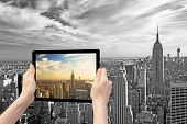 stock photo of monochromatic  - In the bottom left of the photo are hands holding tablet whose screen contains color photo of Midtown Manhattan - JPG