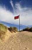 Red Flag On Sand Dune