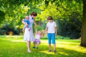 picture of little young child children girl toddler  - Happy family with three kids in a park - JPG