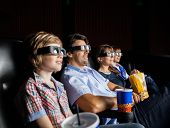 stock photo of watching movie  - Family with snacks watching 3D movie in cinema theater - JPG