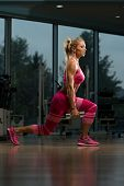 image of squatting  - Middle Age Woman Performing Dumbbell Squats  - JPG