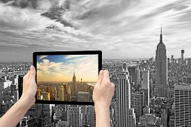 pic of monochromatic  - In the bottom left of the photo are hands holding tablet whose screen contains color photo of Midtown Manhattan - JPG