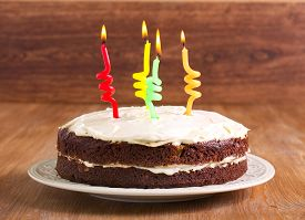 stock photo of hummingbirds  - Hummingbird cake decorated as birthday cake with cream frosting and candles - JPG