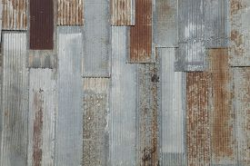 stock photo of rusty-spotted  - Grungy background of a corrugated steel wall with rusty spots on an old building - JPG
