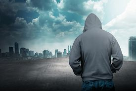 pic of hoods  - Faceless man in hood on the rooftop with city background - JPG