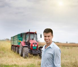 stock photo of tractor-trailer  - Portrait of young attractive businessman in rapeseed field with tractor and trailers in background - JPG