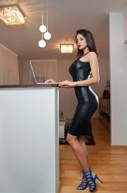 foto of tight dress  - Perfect body woman in short tight fit leather dress working on the laptop in living room - JPG