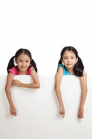 stock photo of identical twin girls  - Happy Asian twins girls behind white blank banner on white background - JPG