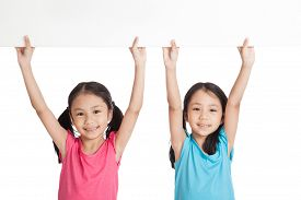 picture of identical twin girls  - Happy Asian twins girls with white blank banner over head on white background - JPG