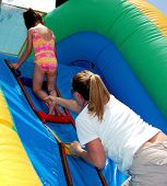 pic of inflatable slide  - Mother giving daughter a helping hand of confidence to continue her path up the inflatable waterslide - JPG
