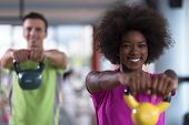 healthy couple  workout with weights lifting  dumbbels at  crossfit gym african  american woman with poster