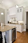 opulent white kitchen with granite countertops and wine fridge